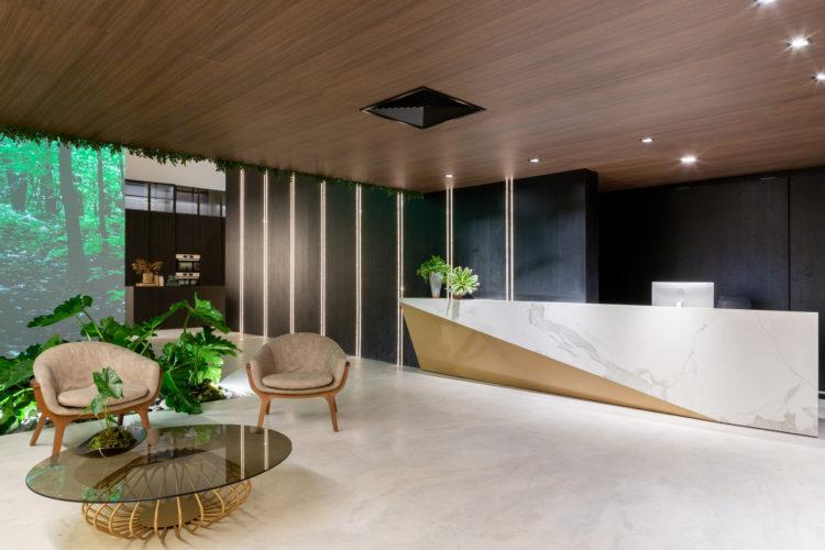 Recepção da loja Dedicatto, bancada em mármore e madeira, piso em mármore e plantas enfeitando.