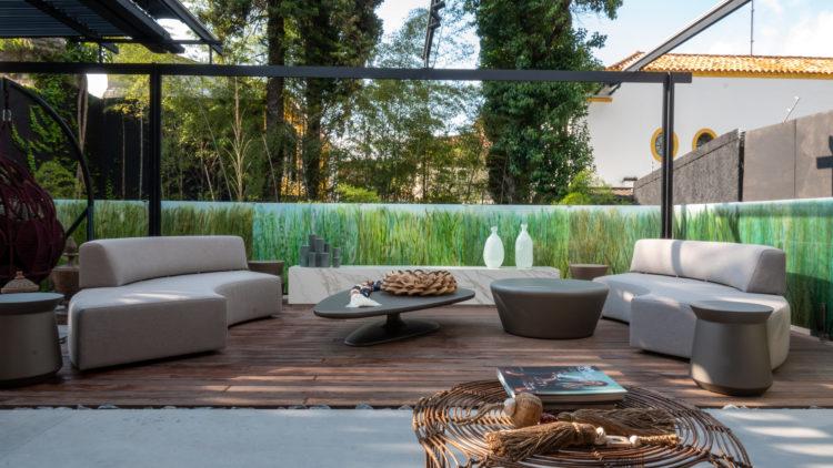 Terraço da loja Dedicatto com sofás curvos claros, deck em madeira e ao fundo, uma pequena vegetação,