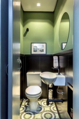 lavabo com meia parede revestida em madeira e pra cima pintado de verde abacate, no piso, ladrilho hidráulico.