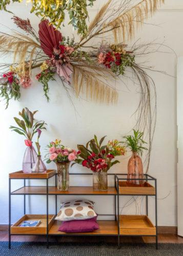 Carrinho de chá com vários arranjos de flores em vasos, e na parede em cima uma arranjo de flores e galhos