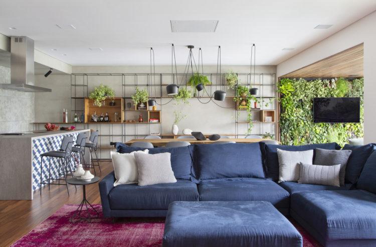 Sala ampla e clara. Com cozinha integrada, ilha na sala. Paredes com pintura imitando concreto, sofá grande na cor azul , atrás da mesa de jantar