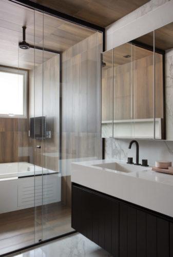 Banheiro com hidro massagem e uma mini tv em frente, todo o espaço do box revestido com porcelanato imitando madeira