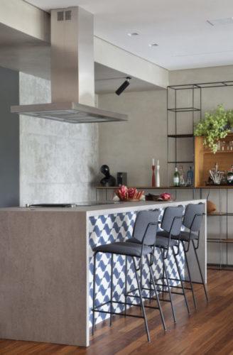 Cozinha integrada com a sala, a ilha revestida de porcelanato cinza e na frente azulejos azul e branco