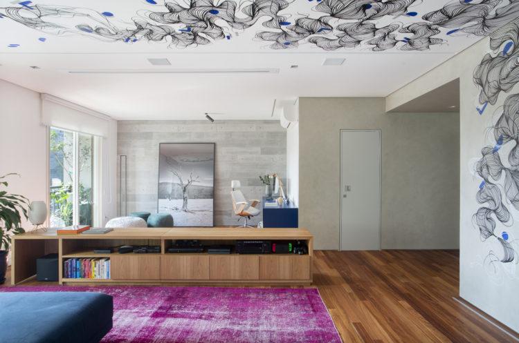 Apartamento com desenho no teto e cozinha rosa choque com neon na parede. Sala ampla, com tapete rosa, bancada baixa em madeira separando ambiente do escritório. E na parede da sala , um desenho feito pela artista plástica Kaju, sobe pelo teto. São tramas de linhas pretas formando um desenho abstrato