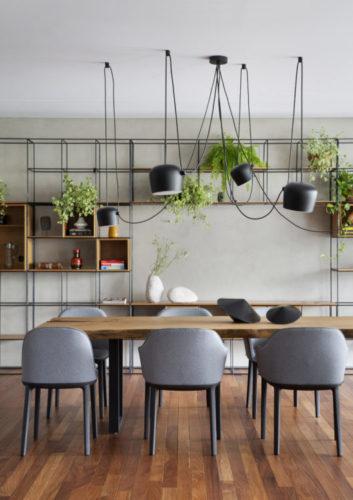 Sala de jantar em madeira com pendentes pretos e cima