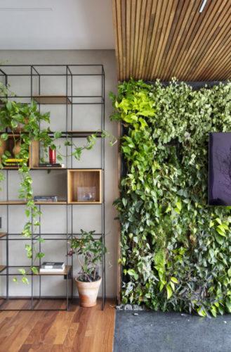 Estante em ferro, desenhada com quadrados, alguns deles recebe um nicho em madeira, e ao lado a varanda com parede verde e uma tv no meio.