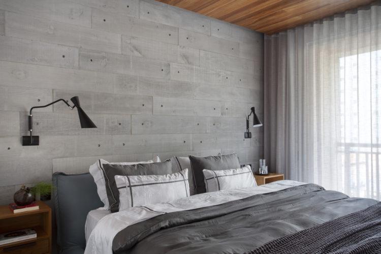 Quarto de casal com parede de fundo da cama revestida com porcelanato imitando cimento, cabeceira e roupa de cama cinza