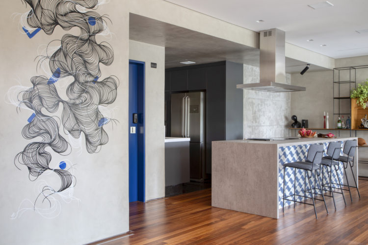 Apartamento com desenho no teto e cozinha rosa choque com neon na parede. Ilha da cozinha na sala, ambiente integrado. Ao lado parede branca com desenho abstrato de preto e branco subindo pelo teto