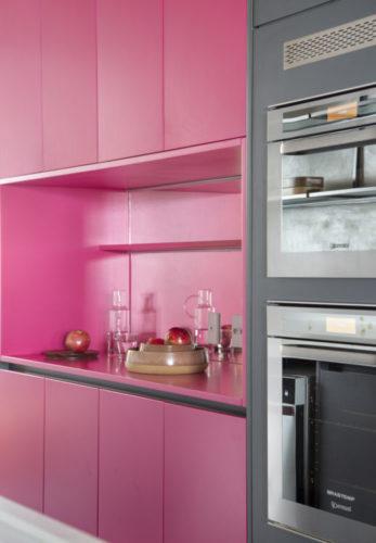 Parte do armário da cozinha todo forrado de cor de rosa choque