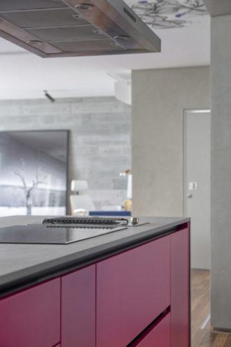 Parte de trás da ilha da cozinha, que é totalmente integrada a sala, tem portas dos armários em rosa choque