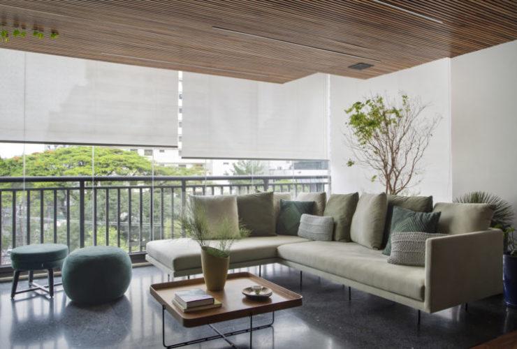 Varanda com teto em ripas de madeira, sofá na cor verde com chaise, varanda fechada com vidro e rolos de cortina