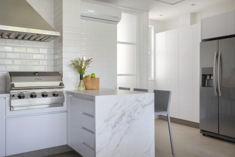 Cozinha revestida com azulejo retangular branco chamado metro , e armários e bancada branca. Uma churrasqueira instalada na bancada