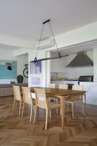 Cozinha aberta para a sala, em frete a mesa de jantar e cadeiras em madeira
