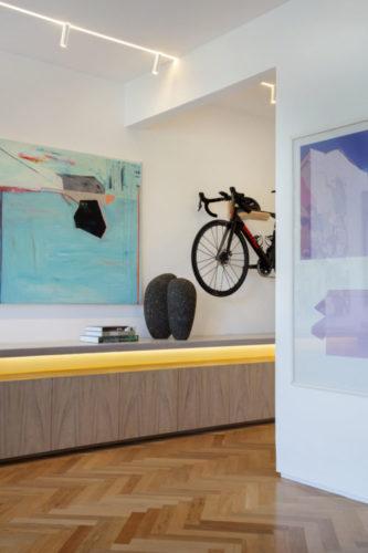 Hall de entrada com um bicicleta pendurada na parede e um móvel baixo em toda a extensão da parede.