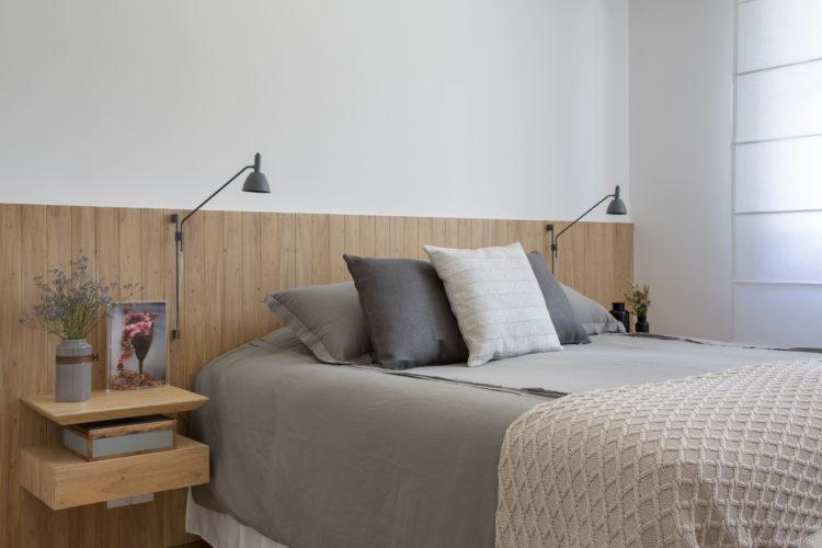 Quarto com cabeceira em madeira , roupa de cama cinza.