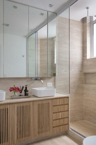 Banheiro revestido em porcelanato imitando mármore, armário embaixo da bancada em madeira ripada.