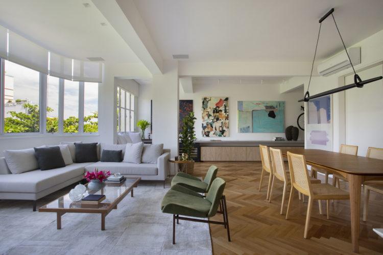 Sala ampla, moveis claros, piso de taco na paginação Chevron, mesa de jantar e cadeiras em madeira. Sala e cozinha integradas