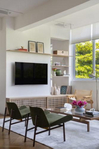Tv na parede, embaixo um rack em madeira, janelas com vista para a copa das arvores.