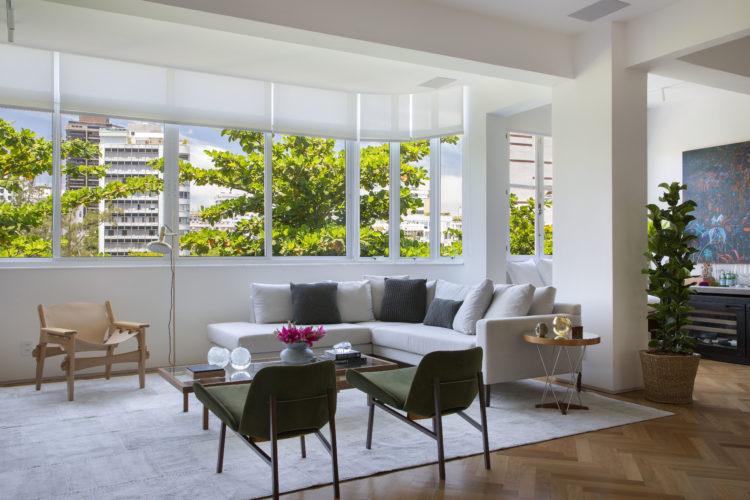 Apartamento no Leblon de 150m2 com sala e cozinha integradas. Sala clara, com grande janelas, sofá em L na cor clara e arvores na paisagem na janela