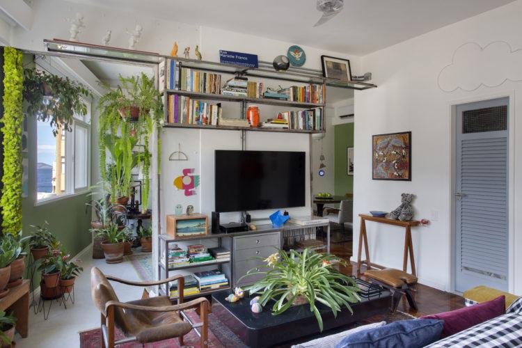 """O estilo """"de tudo um pouco"""" no novo apartamento do arquiteto Francisco Palmeiro. Espaços integrados, apenas com uma parede fazendo divisória para receber uma estante e tv. Perto das janelas que tem vista para o mar, piso frio como se fosse delimitando uma varanda"""