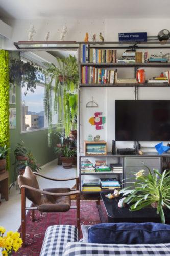Decoração do apartamento em Copacabana tem mistura de estilos, industrial, com as paredes em concreto, urban jungle com muita planta