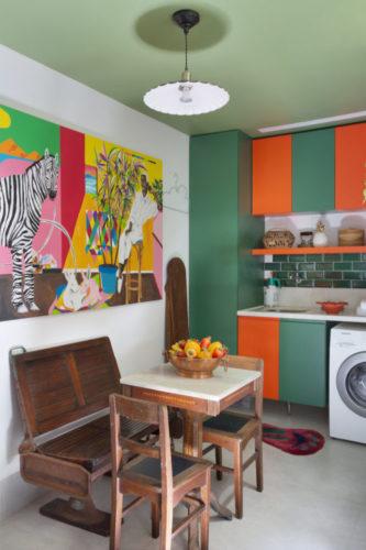 Cozinha com armários na cor laranja e verde, teto pintado de verde e moveis antigos em madeira na copa