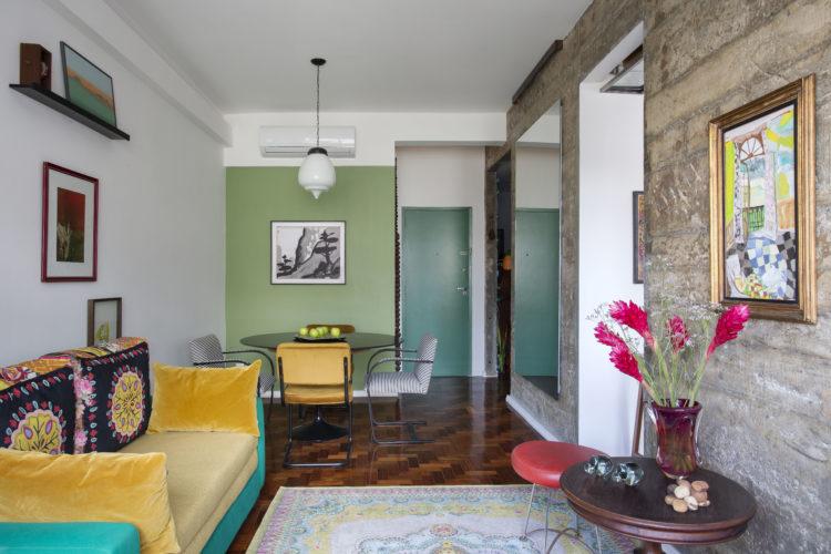 """O estilo """"de tudo um pouco"""" no novo apartamento do arquiteto Francisco Palmeiro. Espaços integrados, parede de pedra , parede pintada de verde e um sofá amarelo"""