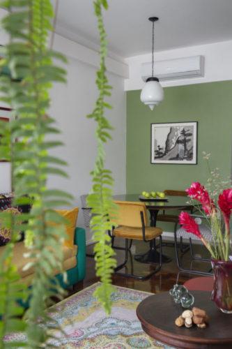 Sala com mesa redonda, muita planta e parede pintada de verde