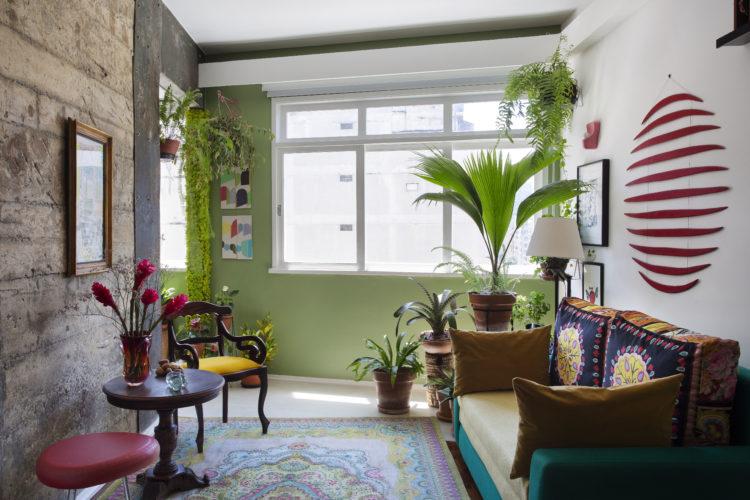 Loft com um parede descascada, parede das janelas na cor verde e o piso em porcelanato.