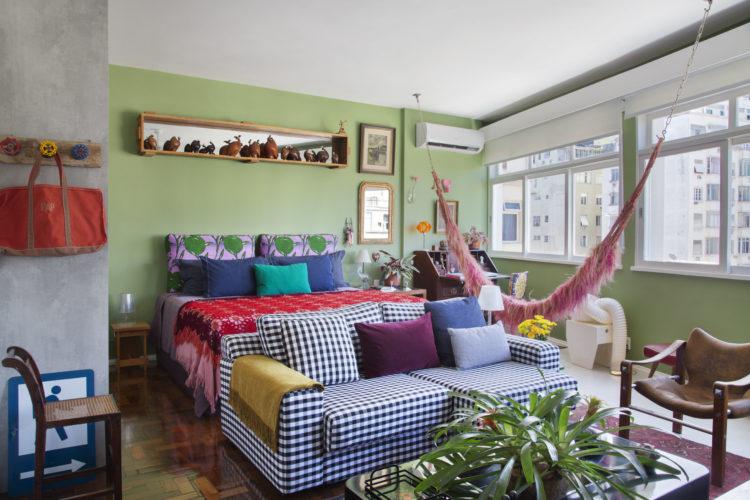 """O estilo """"de tudo um pouco"""" no novo apartamento do arquiteto Francisco Palmeiro. Espaços integrados, em frete a cama um sofá com tecido xadrez, uma rede rosa e a parede de fundo verde"""