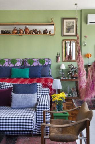 Parede verde atrás da cama, e em cima, um nicho com varias esculturas de Galinha D'angola em madeira