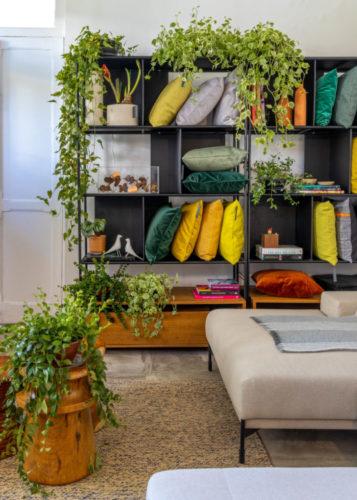 Atelier Botânico - loja carioca reabre com mostra de plantas e a participação de dez paisagistas e floristas. Estante com almofadas coloridas e vários vasos de plantas.