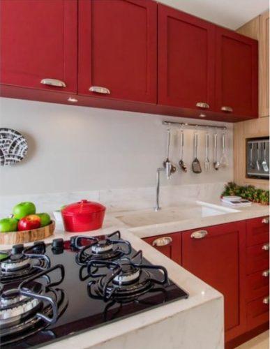 Cozinha com armários na cor vermelha, bancada branca