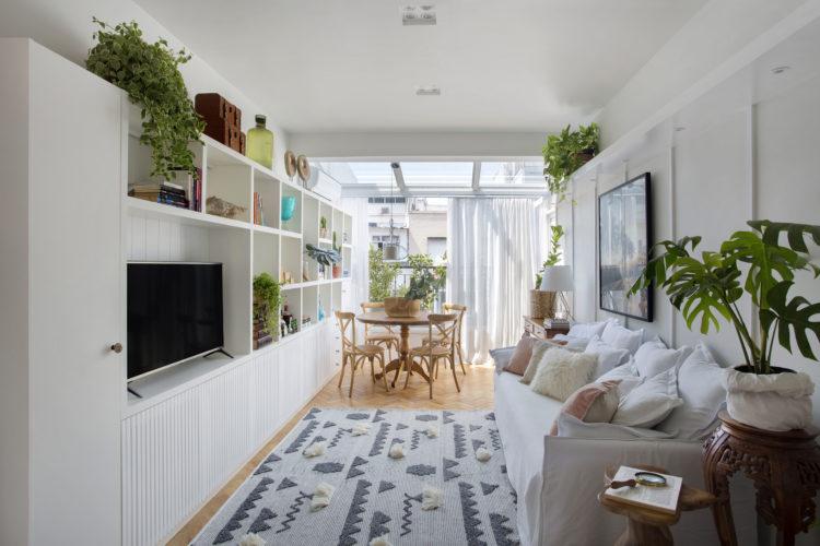 Uma charmosa cobertura no Leme (RJ) com 55m2. Sala clara, ao fundo claraboia fechando a varanda. Sofá branco e em frente estante branca para a tv