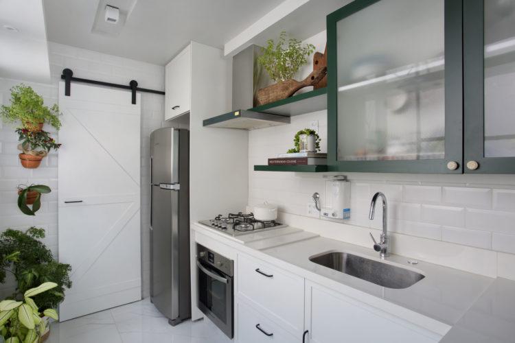 Cozinha com posta de correr em madeira , tudo branco menos o armário superior na cor verde.