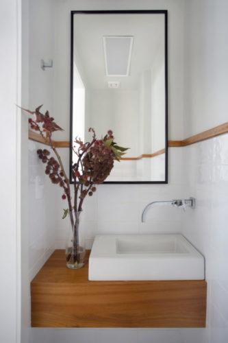 Lavabo com uma mini bancada em madeira, cuba quadrada branca , torneira de parede instalada na lateral