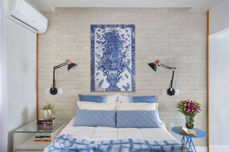 Quarto de casal compacto, parede de tijolinho branca atrás da cama, cama decorada com lençol e almofadas azuis