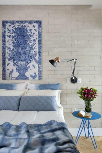Uma charmosa cobertura no Leme (RJ) com 55m2. Quarto do casal com parede da cama revestida de tijolinho branco, uma painel em azulejos branco e azul com a imagem de um vaso de flor, pendurada em cima da cama Mesinha lateral redonda azul e luminária preta articulável na lateral da cama, instalada na parede