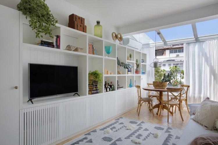 Sala clara, com mesinha redonda em madeira perto da varanda e estante branca para tv e objetos