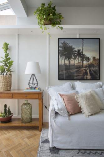 Parede revestida de madeira e pintada de branco com faixas , sofá branco, aparador em madeira rustica e vaso de planta