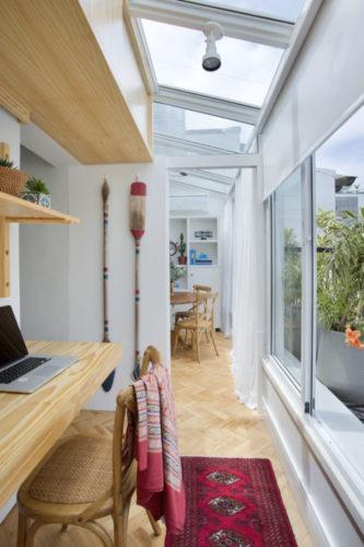 Uma charmosa cobertura no Leme (RJ) com 55m2, espaço do home office bem iluminado, uma claraboia integrando a varanda