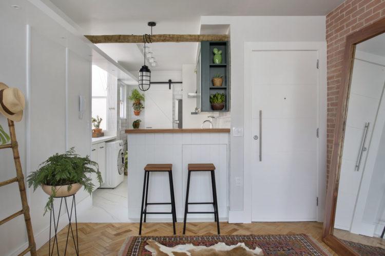 Entrada da cobertura no Leme (RJ) com 55m2, porta branca e ao lado a cozinha aberta , apenas com um balcão separando.