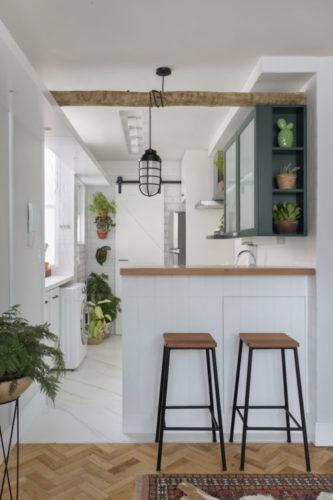 Cozinha branca apenas com os armários superiores na cor verde e cheia de plantas decorando. Um balcão com dois bancos separam da sala