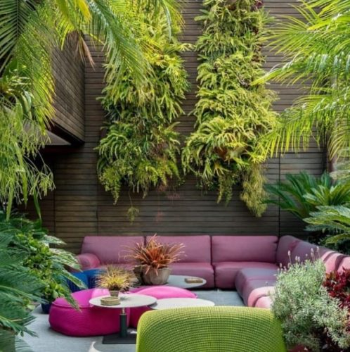 Ambiente externo com uma parede lateral alta e cheia de samambaias, sofá rosa e puffs rosa escuro