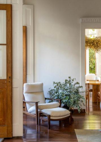 Mostra de plantas em um casarão antigo no Jardim Botânico que é uma loja de mobiliário assinado. Postas altas em madeira com vidro, poltrona branca e ao lado um arranjo de eucalipto