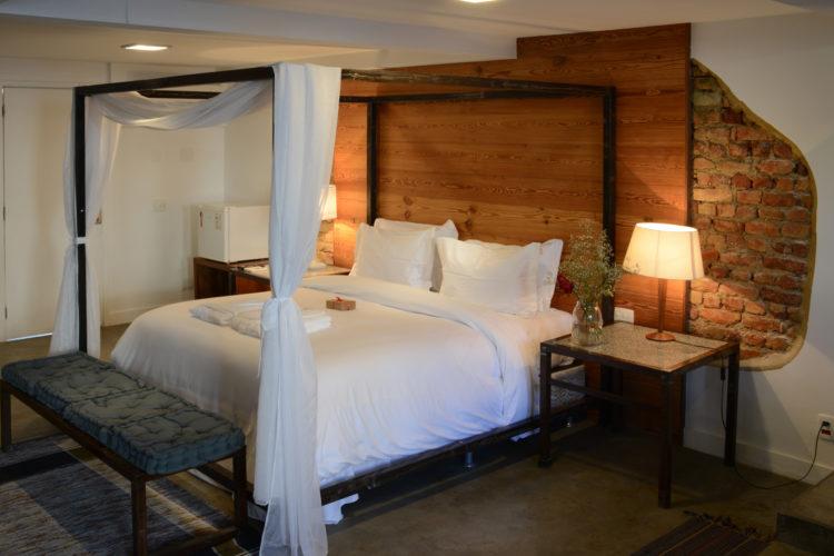 Quarto do hotel Le Chateau Lapa, cama dossel e parede atrás descascada com tijolo aparente