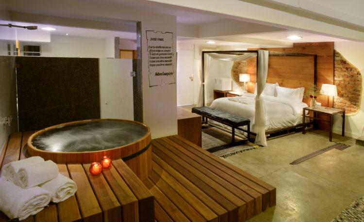 Quarto do hotel Le Chateau Lapa, cama dossel e um ofuro no deque de madeira