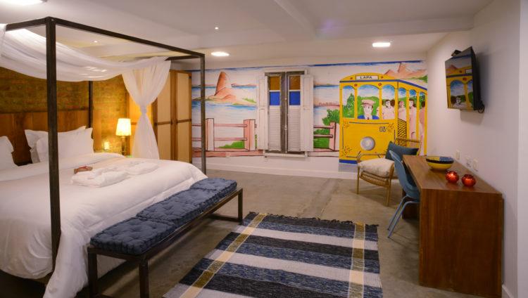 Quarto no hotel Le Chateau Lapa, no bairro com mesmo nome. Quarto amplo, com cama dossel , na parede uma pintura com o bondinho e uma janela antiga colocada.