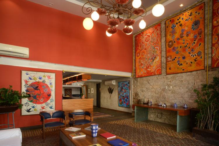 Recepção do hotel Le Chateau Lapa, no bairro da Lapa. Pé direito alto, uma parede de pedra, a outra pintada de vermelho