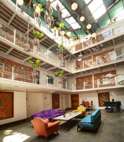 Grande vão, do lado de dentro, no meio do prédio de três andares do Hotel Le Chateau Lapa. Na parte de baixo sofás coloridos , um roxo, outro turquesa e um piano ao fundo
